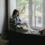 Woman-reading-bible-on-window-ledge